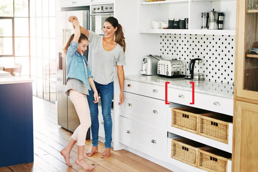 mother and daughter dancing in a kitchen