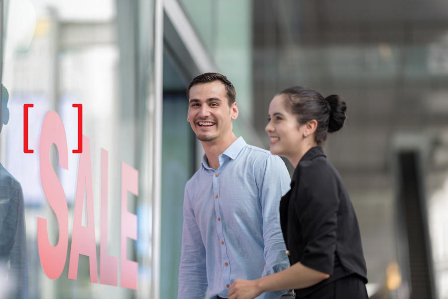 Woman and man excited looking into shop with shop window display with text SALE on red poster