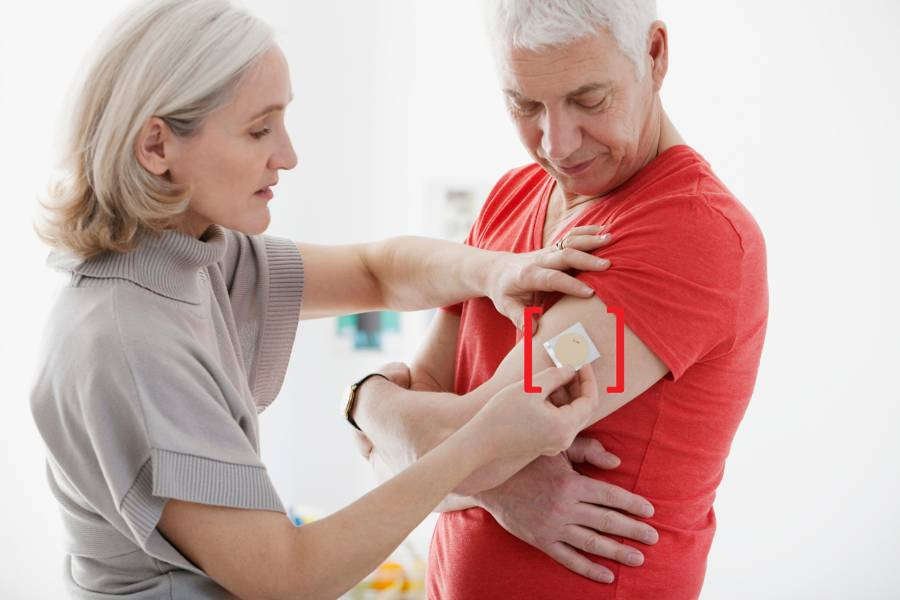 woman applying a patch to a man's arm
