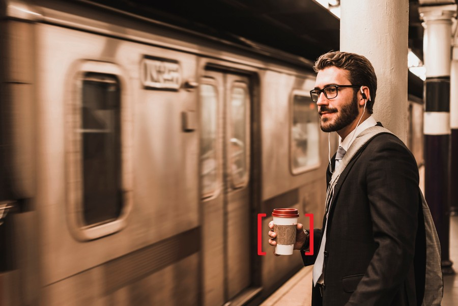 man holding a coffee cup next to a subway train
