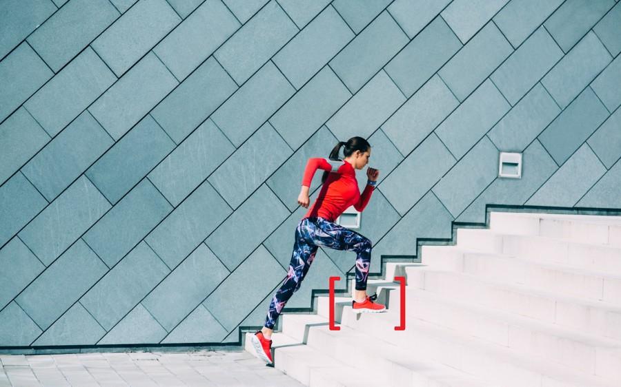 Mulher exercitando-se em uma escadaria na cidade