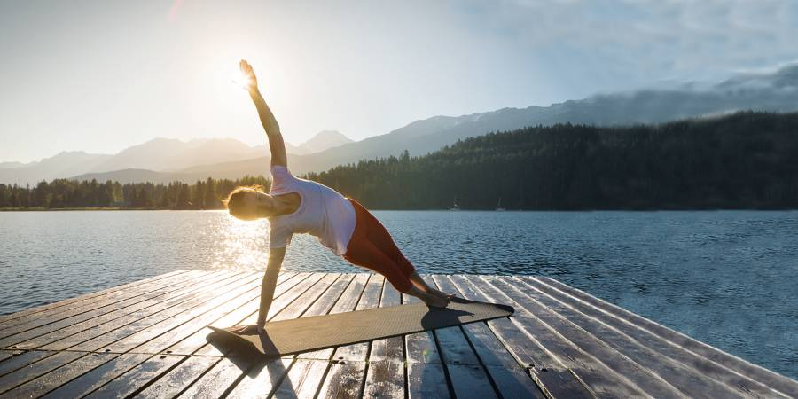 woman doing yoga on a dock