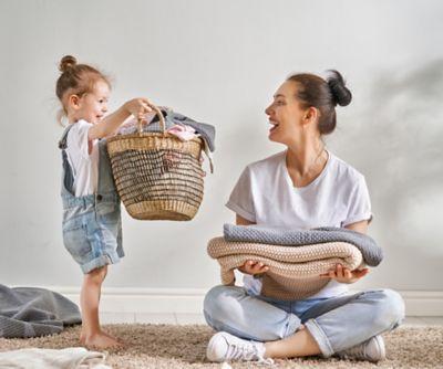 Prace domowe z dziećmi, matka i córka składają razem pranie