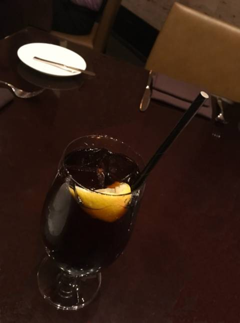 paper straw in a glass of coke with a piece of lemon