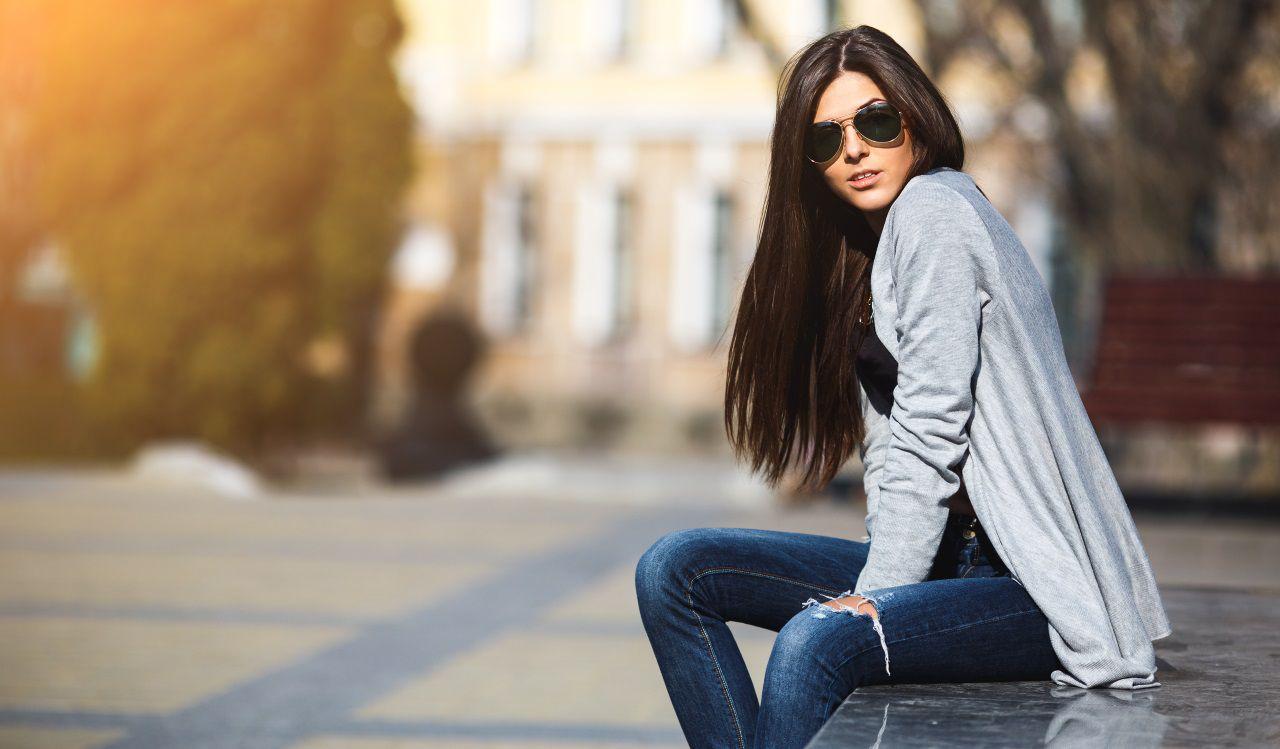 Ragazza con capelli lunghi castani e occhiali da sole seduta su una panchina
