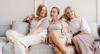 Drei Frauen mittleren Alters, alle in zarten Pastelltönen gekleidet, sitzen in entspannter Haltung auf einer grauen Couch, die vor einer pastellrosa Wand steht