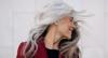 Portraitaufnahme einer reifen Frau mit schwarzem Top und rotem Blazer, die den Kopf mit geschlossenen Augen lächelnd zur Seite neigt – ihre langen grauen Haare fliegen um ihr Gesicht