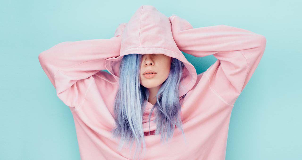 Frau mit Haaren in Pastellviolett und rosa Hoodie streckt Hände an den Kopf