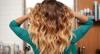 Frau mit langen, lockigen Haaren im Ombré-Look in türkis-schwarz kariertem Hemd steht mit dem Rücken zur Kamera – im Hintergrund ist ein Spiegel mit zahlreichen Haarpflegeprodukten zu sehen