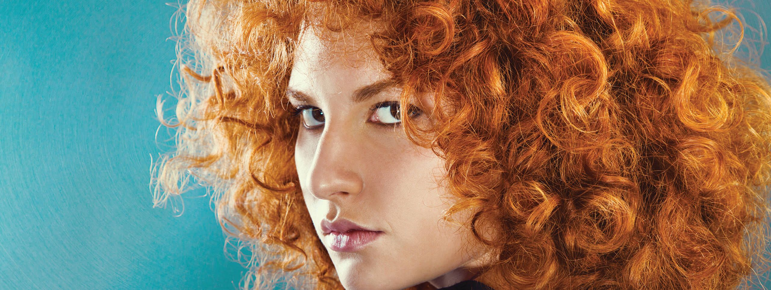 Woman rocks big curly hairstyle for red hair