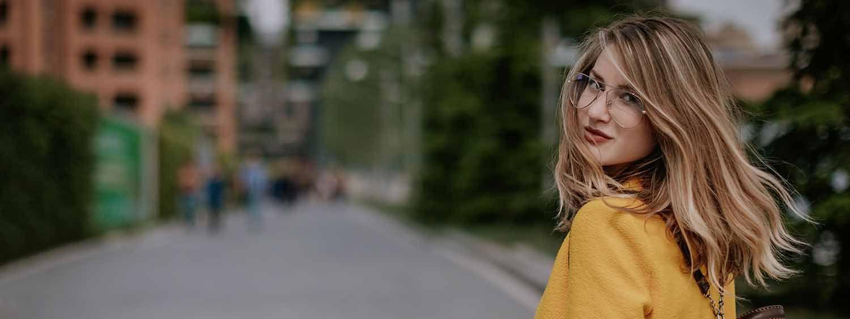 Femme blonde avec des lunettes et un manteau jaune en train de marcher