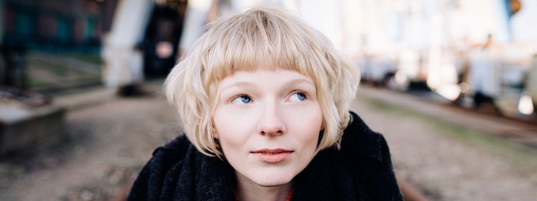Femme aux cheveux blonds coupés courts et des yeux bleus