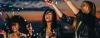 Junge Frauen in Partykleidern feiern ausgelassen und schmeißen Konfetti