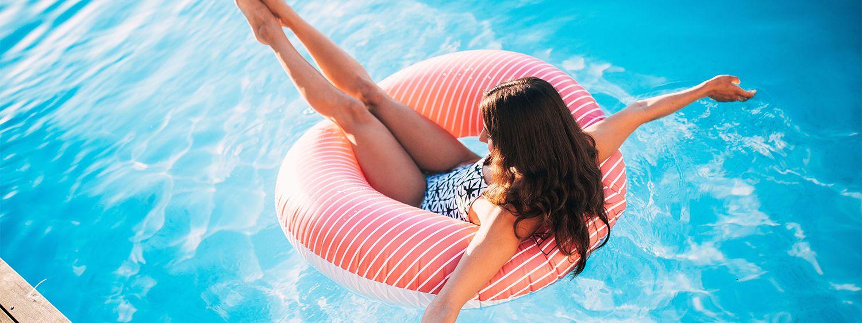 Braunhaarige Frau auf einem großen Schwimmring im Pool