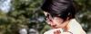 Schwarzhaarige Frau mit kurzen Haaren trägt Sonnenbrille