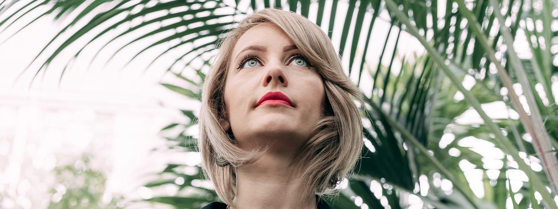 Blonde Frau mit asymmetrischem Bob mit Seitenscheitel