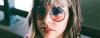 Blonde Frau mit Long Bob und Pony trägt eine runde Sonnenbrille mit farbigen Gläsern