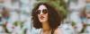 Dunkelhaarige Frau im Sommer-Outfit mit Sonnenbrille und Dauerwelle