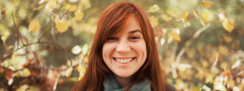 Jeune femme rousse avec une mèche sur le front en train de sourire au photographe