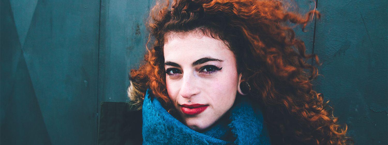Frau mit lockigen, roten Haaren blickt in die Kamera und trägt roten Lippenstift und einen blauen Schal