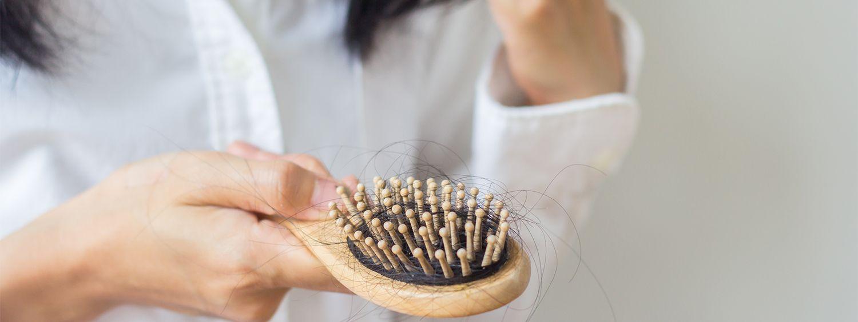 Gros plan sur une femme tenant une brosse à cheveux en bois recouverte de cheveux bruns.