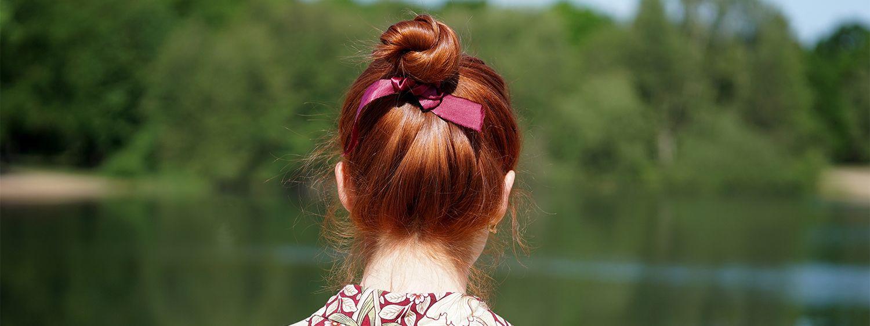 Rothaarige Frau mit gemusterter Bluse schaut auf einen See und trägt einen Dutt mit pinker Schleife