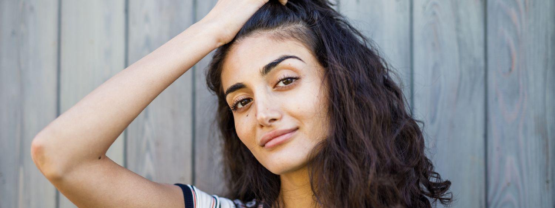 Frontansicht einer Frau mit dunklem, lockigem Haar