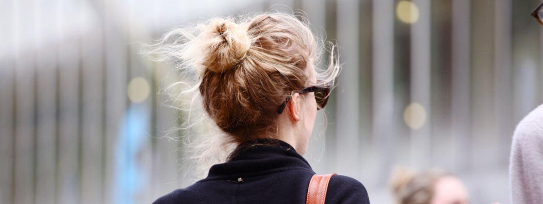 Blondynka w koczku i okularach przeciwsłonecznych odwróca tyłem