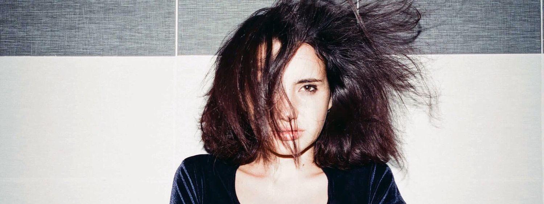 Dunkelhaarige Frau sitzt im Schneidersitz und föhnt sich die schulterlangen Haare von unten