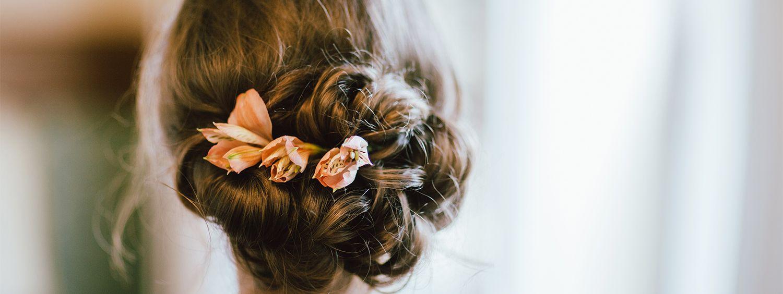 Kobieta z kwiatami wpiętymi w eleganckie upięcie