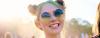 Porträt eines blonden, lächelnden Mädchens mit Double Buns, Sommersprossen und Sonnenbrille