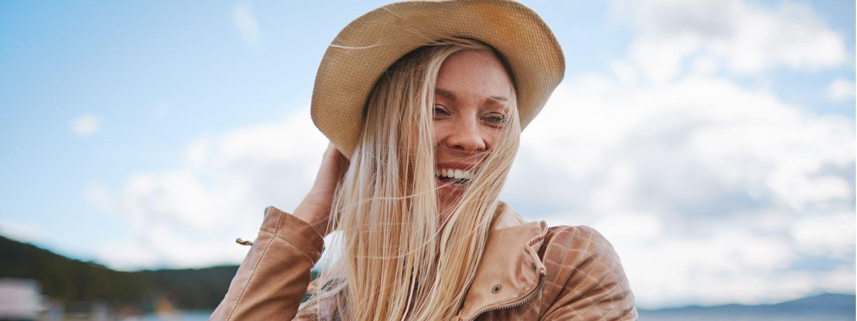 Femme blonde souriante se trouvant au bord de la mer