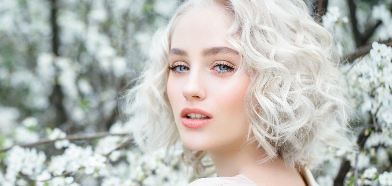 Jeune femme avec un carré bouclé blanc dans une forêt enneigée