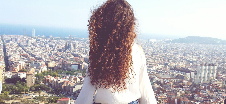 Femme brune aux cheveux bouclés vue de dos avec panorama sur une ville et la mer