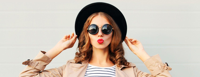 Femme rousse avec du rouge à lèvres portant un chapeau et des lunettes de soleil