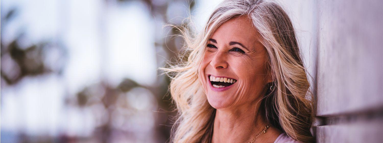 Femme aux longs cheveux gris en train de sourire