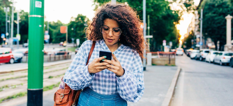 Femme aux cheveux longs et bouclés en train de regarder sur son portable
