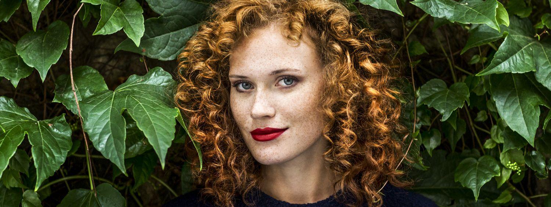 Femme rousse aux cheveux bouclés avec un rouge à lèvres rouge intense