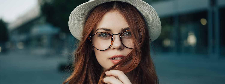 Donna con capelli lunghi rossi, riga in mezzo, occhiali e cappello
