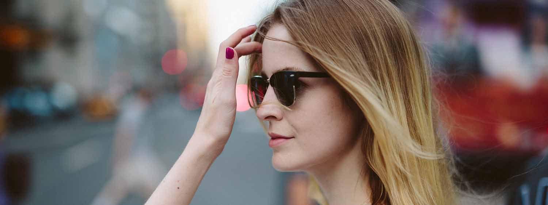 Donna con punte schiarite e occhiali scuri