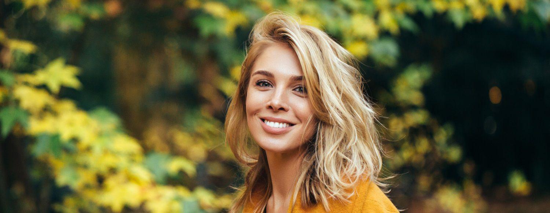 Donna in colori autunnali con capelli biondi e riga di lato