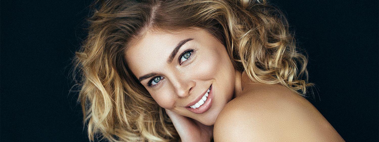 Lächelnde braunhaarige Frau mit Strähnen in Blond