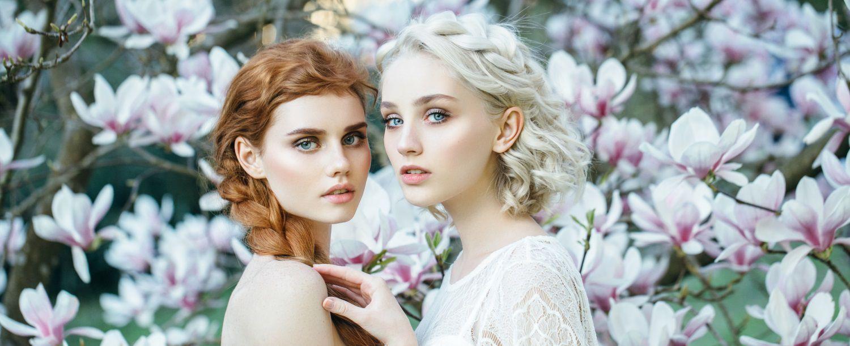 Due giovani donne vestite di bianco con capelli mossi