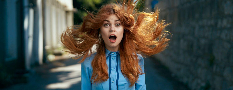 Donna con capelli rossi lunghi al vento e vestito azzurro