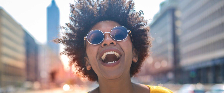 Donna con maglietta gialla e capelli afro