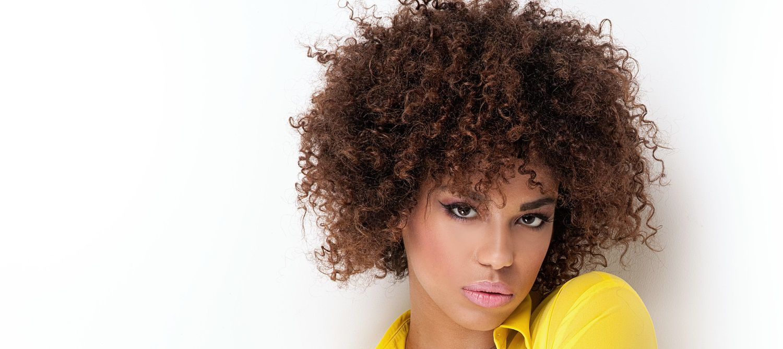 Donna con camicia gialla sgargiante e capelli afro