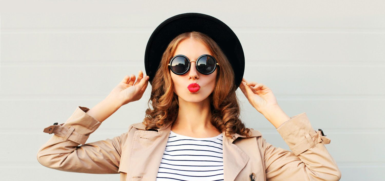 Donna con capelli rossi lunghi, boccoli, cappello e occhiali scuri neri, rossetto rosso e stile casual
