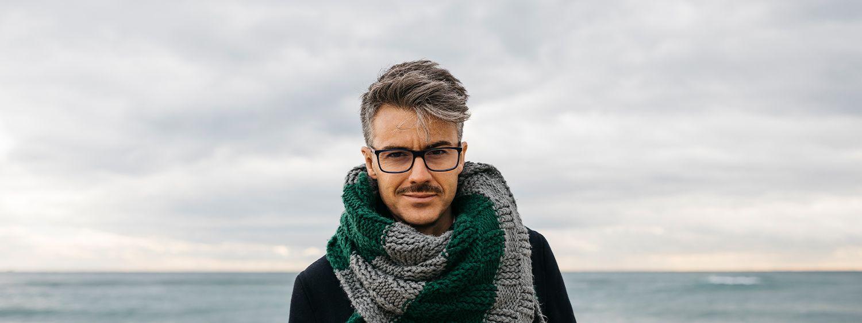 Uomo con capelli brizzolati, occhiali e baffi, con alle spalle il mare