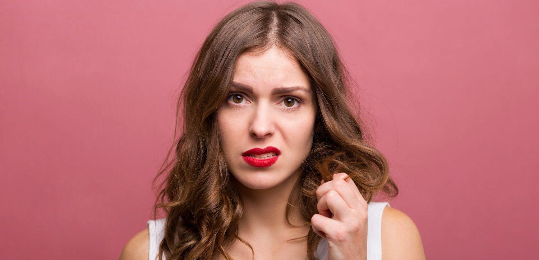 Donna che afferra una delle proprie ciocche di capelli con aria poco soddisfatta