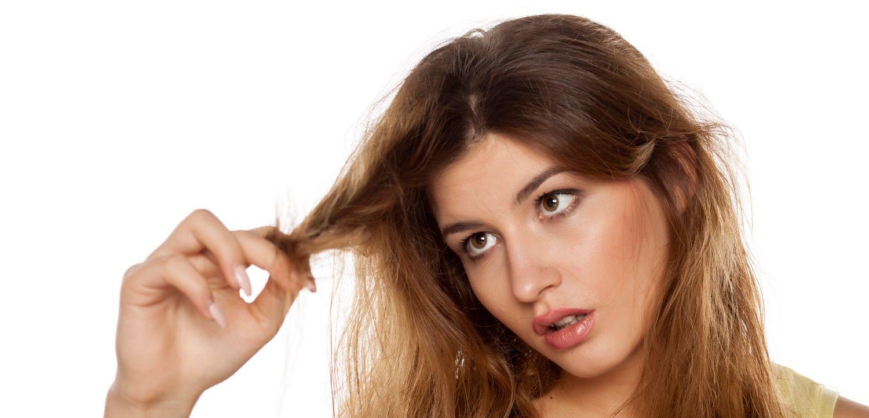 Donna con capelli lunghi rossi che guarda con fastidio le proprie ciocche crespe